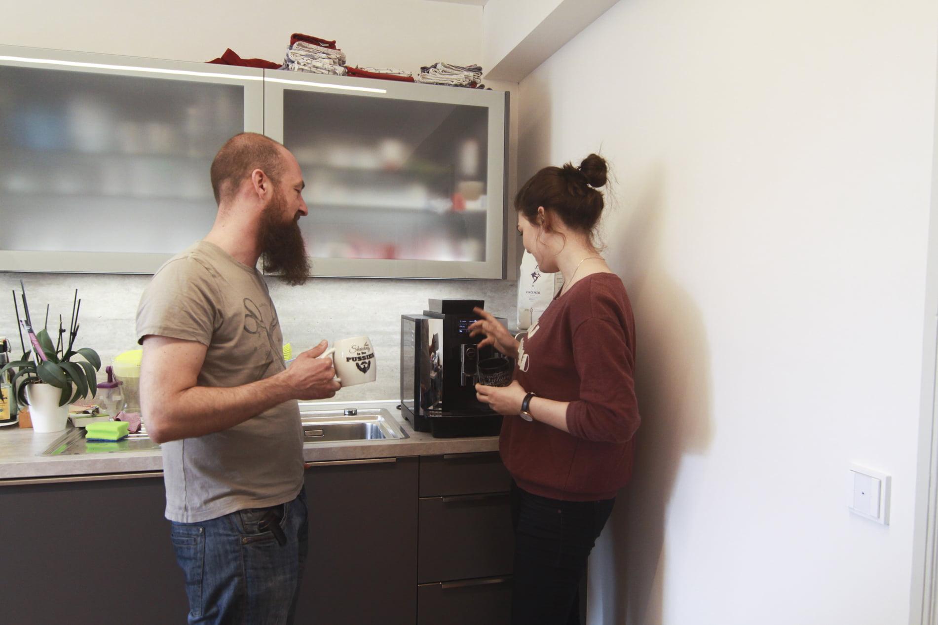 Zwei Mitarbeiter im Büro zapfen an einem Kaffeevollautomaten Kaffee für ihre Arbeit im Büro.
